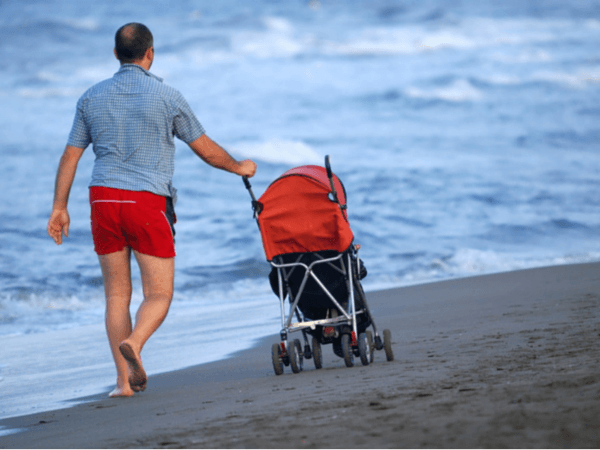 pushing stroller on the beach